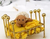 Cute little sleepy lamb in a bed with a bright yellow chenille bed spread