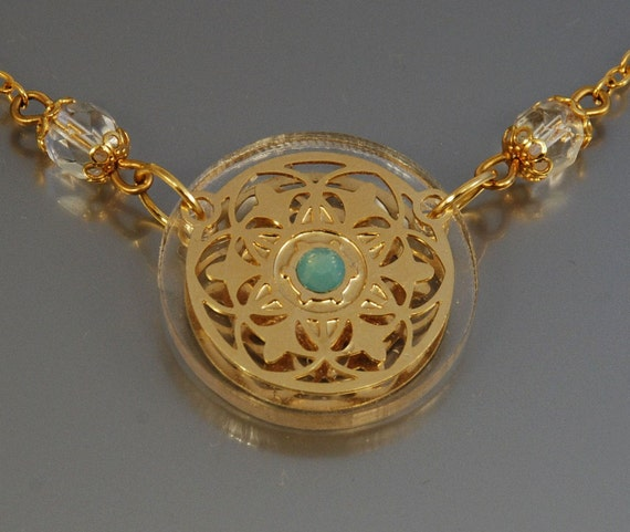 Gold patterned circle necklace and greenish Swarovski. Unusual and unique. Handmade by Tuliya