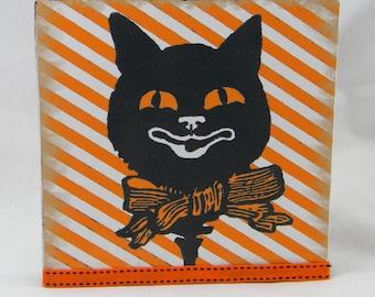 Vintage black cat Halloween decor on wood panel