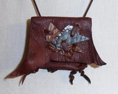 Origins---This Wisdom Pouch is made out of Bordeaux colored leather with a unique pattern on the flap that features Fish Hide Leather