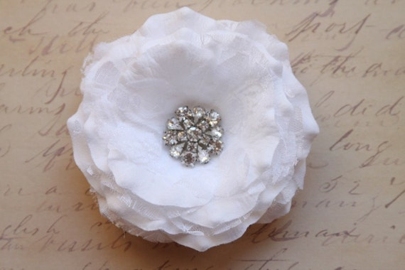 A beautiful white rose embedded in white lacing with a rhinestone