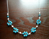 The Less Showers More Flowers- Silver Necklace with White Faceted Beads and Flowers Made of Bright Blue Beads
