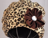 Cheetah print infant cap with interchangeable flower clip.