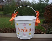 Personalized white metal bucket with orange pink and yellow designs and orange polka dot ribbon bow
