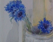 Blue cornflowers in a stoneware jar