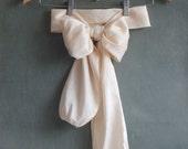 Cream taffeta bow belt and magnolia flower brooch