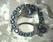 Vintage blue rhinestone circle brooch floral motif