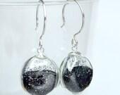 Black fine glitter in round blown glass earrings.