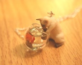 Mischievous Siamese Kitty cat is playing with goldfish in a fish bowl necklace