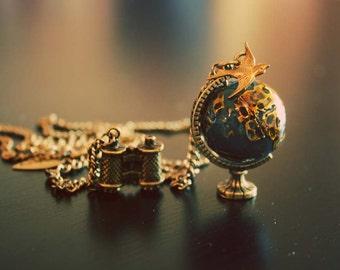 Around the world golden bird on the Globe with binocular necklace