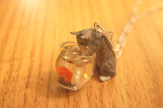 Mischievous Gray Kitty cat is playing with goldfish in a fish bowl necklace