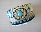 Bohemian hippie bracelet with a turquoise blue friendship bracelet and rhinestones on a leather cuff base
