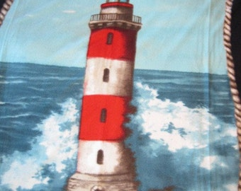 Light House and Crashing Waves with Red Fleece Blanket