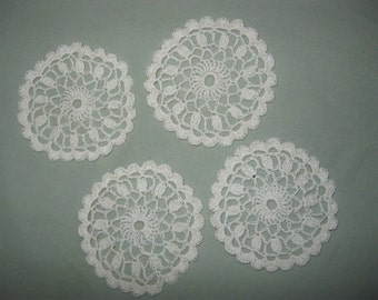 Four small ecru crocheted doilies