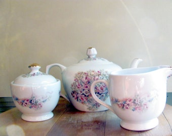 Teaset with teapot and sugar bowl and creamer with pink roses and blue and yellow blossoms