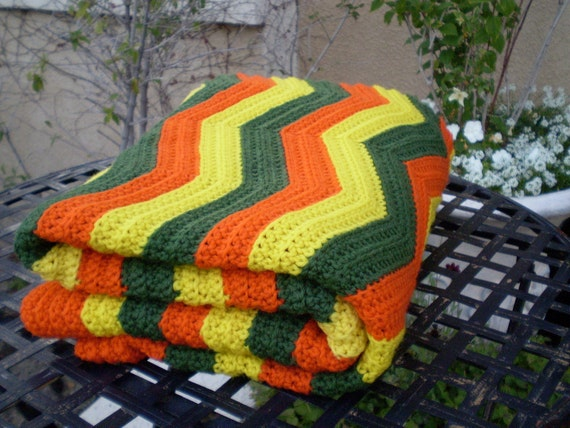 A vintage 1960s 1970s orange yellow and green chevron pattern knit crochet afghan granny blanket