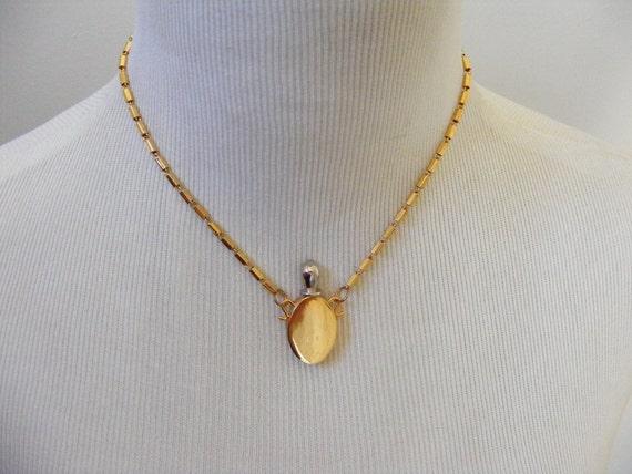 Vintage Secret Perfume Bottle necklace pendant 1970s. Gold metal Oval bottle with separate stopper on chain. Unworn.