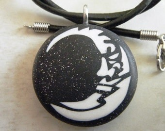 Moon hand carved on a polymer clay starry night background.  Pendant comes with a FREE necklace