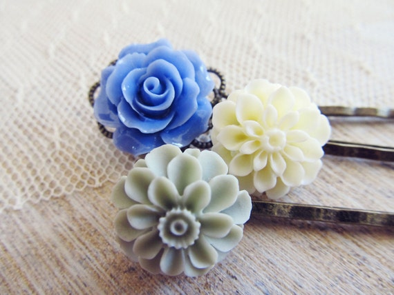 A trio of vintage inspired floral hair pins in soft gray, creamy white and cornflower blue