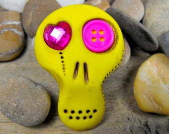 Mini sugar skull in yellow with pink asymmetric eyes: a heart and a button. Brooch, keychain, pendant or magnet (you choose)