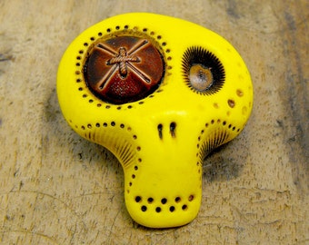 Yellow sugar skull with a brown vintage button in his eye. Brooch, keychain, pendant or magnet (you choose)