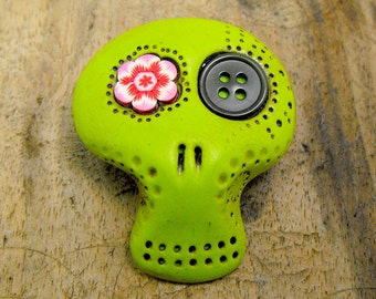 Lime green sugar skull with a pink flower and a black button inside his eyes. Brooch, keychain, pendant or magnet (you choose)