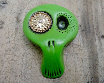 Avocado green skull with a vintage golden button in his eye. Brooch, keychain, pendant or magnet (you choose)