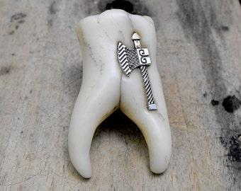 Human tooth brooch or fridge magnet with a tiny metal ax inside it. A huge molar with two roots. Just a little bit dirty and very funny