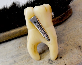 Human tooth brooch with a tiny toothpaste tube inserted. Do'nt forget to clean your teeth every day, little monster