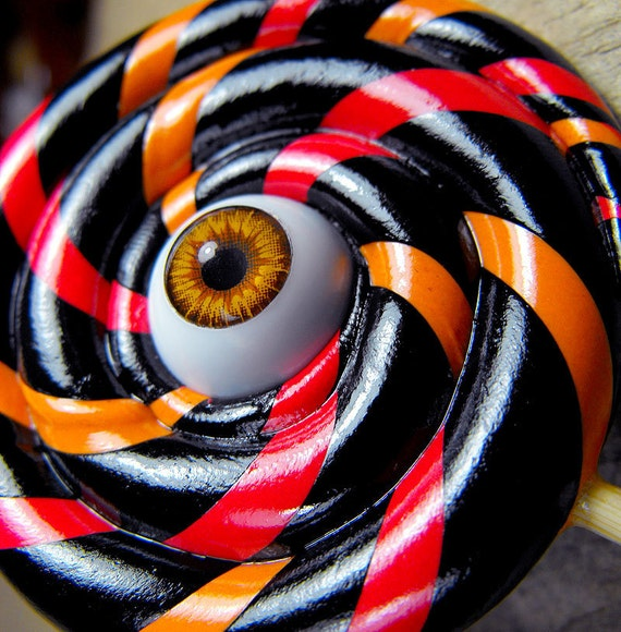 Lollipop brooch whit its own central eye. Black, orange and red. Crazy, funny and just a little creepy