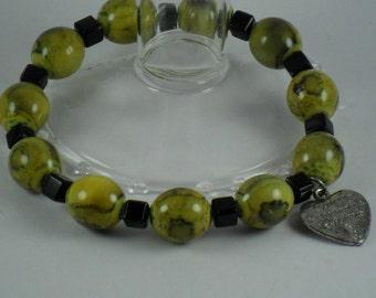 Stretchy Yellow and  Black smokey swirled beaded bracelet with  cancer awareness charm