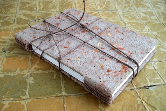 Handmade banana peel and onion skin paper covered journal with cord closure. Hand bound with sketch paper.