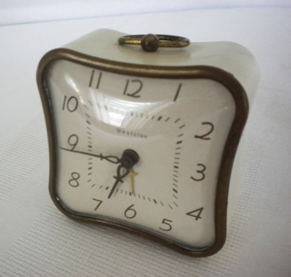 Vintage wind up clock with alarm. Curved, metal, cream colored case, lovely aged patina on brass trim. Marked Westclox La Sallita.