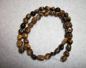 tigereye (natural), large pebble,  Sold per 16-inch strand.