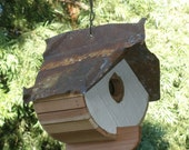 Birdhouse with white front and rusted metal roof