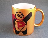 11oz Super Panda with red coat cloak and P letter on a belly golden ceramic mug cup. Customized cups mugs available.