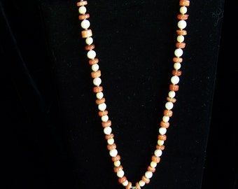 Fun orange and ivory colored necklace with pendant and earrings