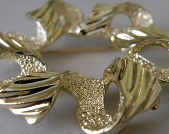 20% off Sarah Coventry ribbon brooch pin. Gold tone metal.Textured.