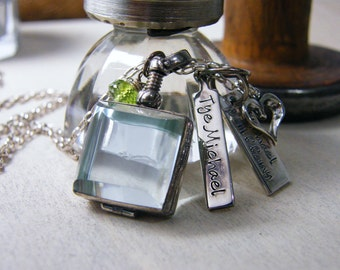 personalized glass locket with hand stamped baby name, wedding couple and date tags, heart and peridot