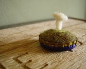 Felted white mushroom in a blue and brown bottlecap