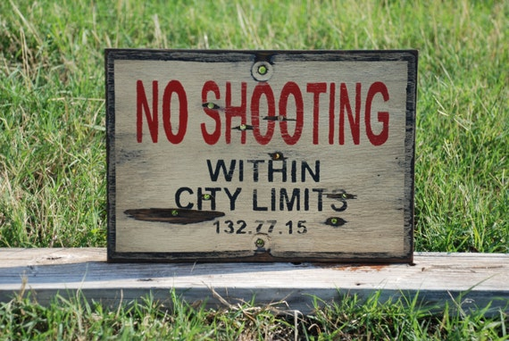Wooden sign No shooting within city limits sign made from reclaimed plywood