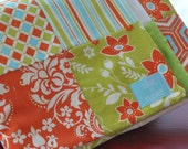 modern baby quilt in orange green and blue