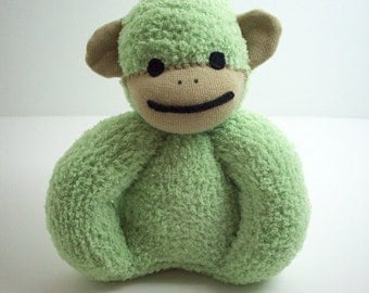 A Sock Monkey Baby Toy in Green and Tan