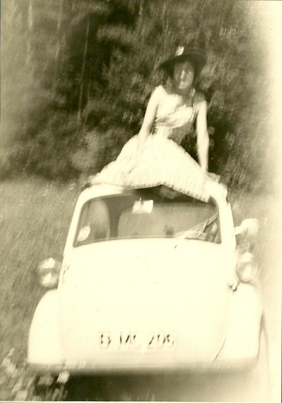 Vintage black and white 1950s photo of some blurry people and a car