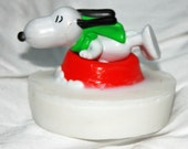 Snoopy on a sled sliding down white glycerin soap right into your bath tub