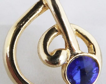 Vintage jewelry brooch in gold tone with faux blue sapphire in musical clef brooch