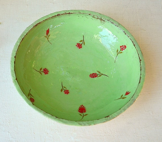 An apple-green bowl with red flowers