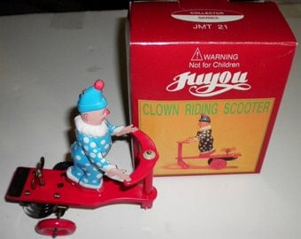 Juyou Clown Riding Scooter Vintage Tin Wind Up Toy, 1980s