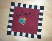 Heart stitched wall art titled Follow