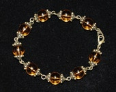 Beautiful 8 inch bracelet with round amber beads and antique gold tone bead caps